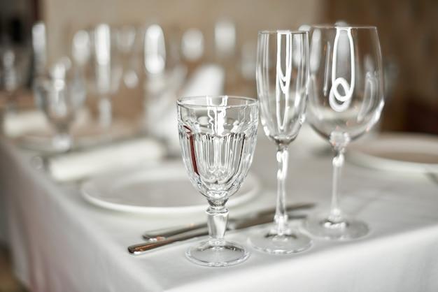 Красиво оформленный праздничный стол с тарелками и бокалами в ресторане