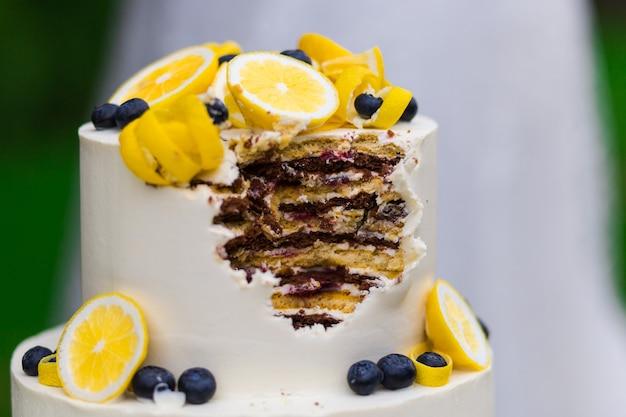 Красиво оформленный откушенный торт на подставке на свадебной церемонии на открытом воздухе