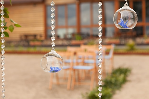 Beautifully decorated outdoors ceremony area with brown chairs on blur background