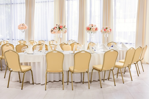 Beautifully decorated room with covered tables with flowers in the restaurant