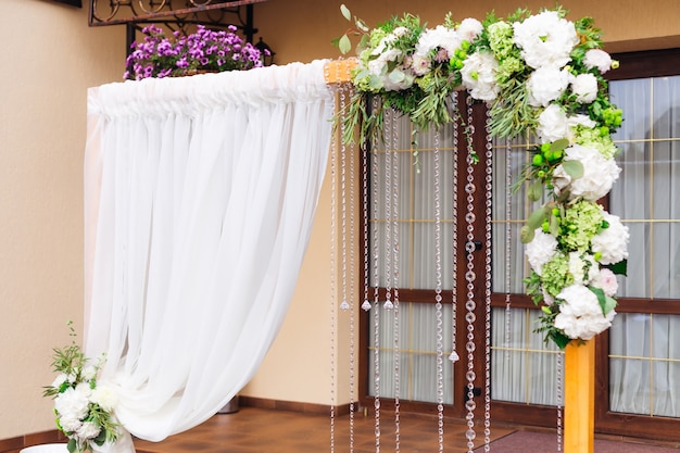 Красиво оформленная выездная церемония у стеклянных дверей ресторана деревянная арка с цветочной композицией из тюля и цепочки с прозрачными бусинами.