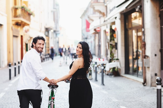 Beautifully dressed man and woman are walking in the old city with a bicycle.