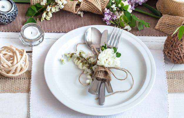 休日のための美しくエレガントな装飾が施されたテーブル-モダンなカトラリー、弓、ガラス、キャンドル、ギフトを備えた結婚式やバレンタインデー