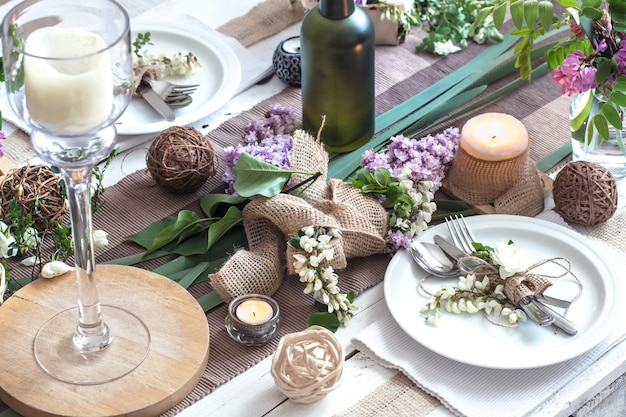 Красиво элегантно оформленный стол для праздника с весенними цветами и зеленью - свадьба или день святого валентина с современными столовыми приборами, бантом, бокалом, свечой и подарком, горизонтальный, крупным планом, тонированный
