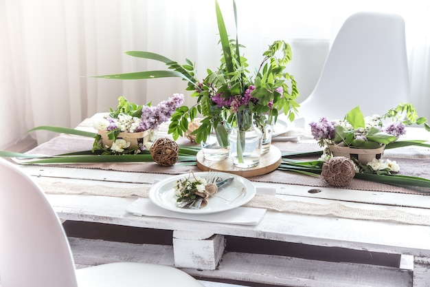 Beautifully elegant decorated table for holiday - wedding or valentine day with modern cutlery, bow, glass, candle and gift