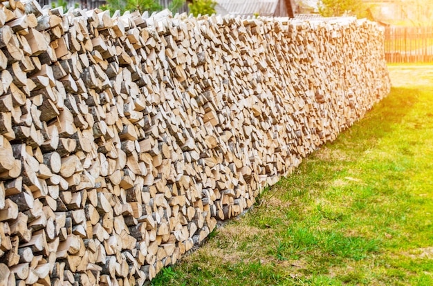 Beautifully folded stack of wooden wood on the lawn in the village of countryside.