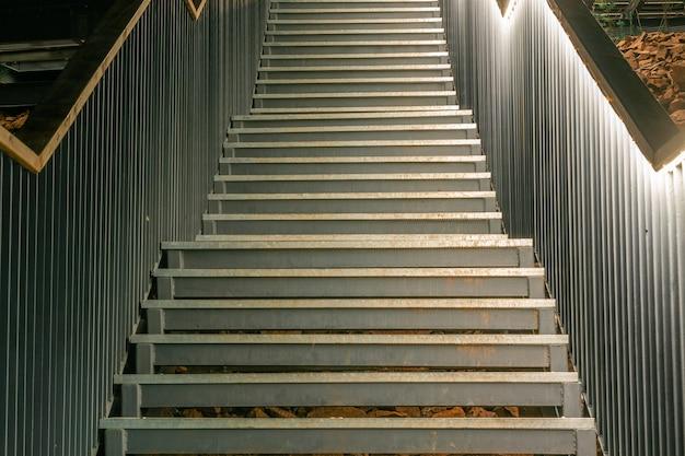 위쪽으로 이어지는 아름답게 조명된 스테인리스 스틸 계단