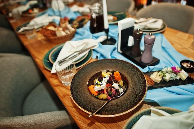 レストランで食べ物、グラス、電化製品を備えた美しく置かれたテーブル。