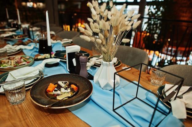 레스토랑에 음식, 안경 및 가전 제품이 있는 테이블을 아름답게 배치했습니다.