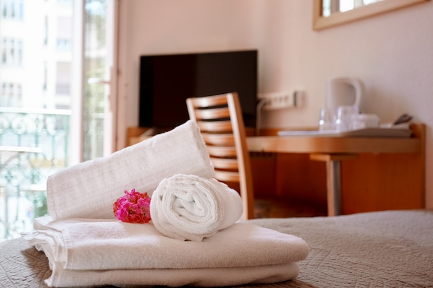 Beautifully and neatly folded white towels on the bed decorated with a bright pink flower