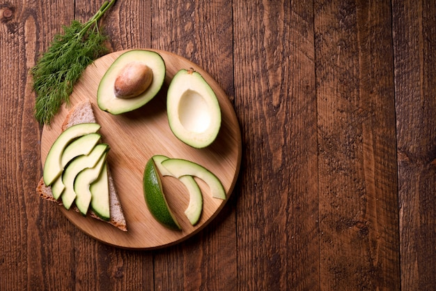 Beautifully plated avocado toast with delicious-looking toppings on wooden brown background.