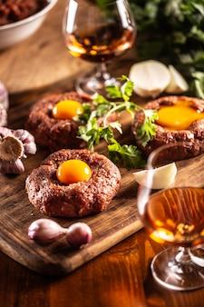 아름답게 준비된 쇠고기 스테이크는 식욕을 돋우는 달걀 노른자를 곁들인 타르타르 요리입니다. 마늘, 양파, 허브 및 알코올과 함께 음료로 제공됩니다. 백그라운드에서 원시 고기의 전체 흰색 그릇.