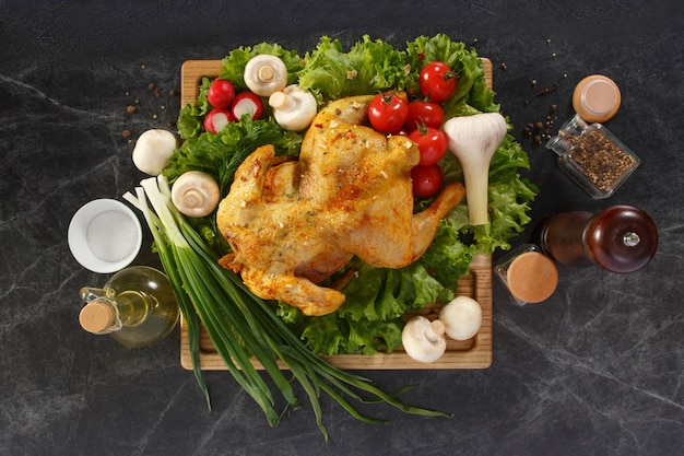 Beautifully served roasted chicken garnished with fresh tomatoes, green salad, radish and greens