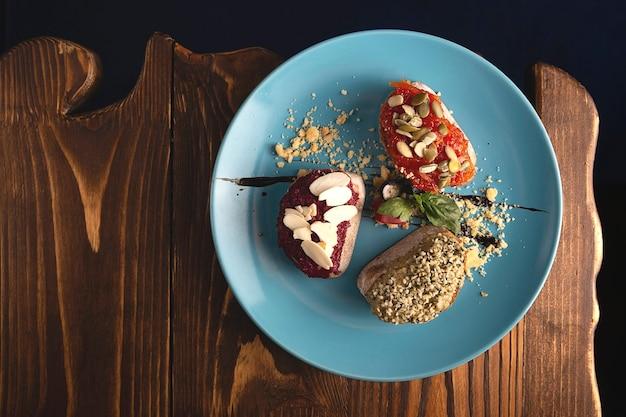 Красиво поданная вегетарианская брускетта из свеклы, помидора, хумуса с охрой и семенами