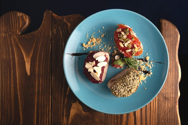 Beautifully served vegetarian bruschetta made from beetroot, tomato, hummus with ocher and seeds