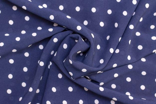 濃い青色の背景に白い水玉模様のパターンで美しくねじれた生地。布のテクスチャ