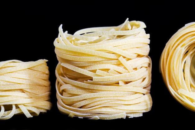 Красиво скрученная пшеничная лапша в форме гнезда из высококачественной муки твердых сортов пшеницы, макаронных изделий или лапши крупным планом