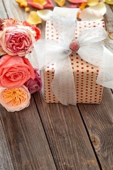 발렌타인 데이 또는 여성의 날을위한 아름답게 포장 된 선물 상자와 신선한 장미. 휴일 개념.