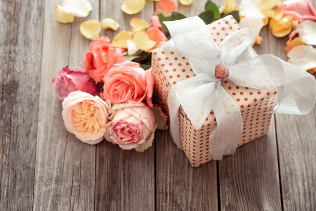 Красиво упакованная подарочная коробка и свежие розы. концепция праздника.