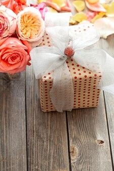 Красиво упакованная подарочная коробка и свежие розы на деревянном фоне