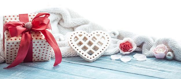 Красиво завернутый подарок на день святого валентина и милые детали праздничного декора на деревянной поверхности.