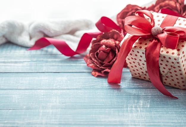 Красиво завернутый подарок на день святого валентина и элементы декора на деревянной поверхности заделывают.