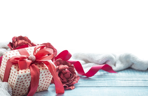 Beautifully wrapped valentine's day gift and decor elements on a wooden surface close up.
