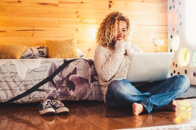 美しい若い大人の女性は彼女の足に現代のラップトップコンピューターで自宅でテクノロジーを使用しています