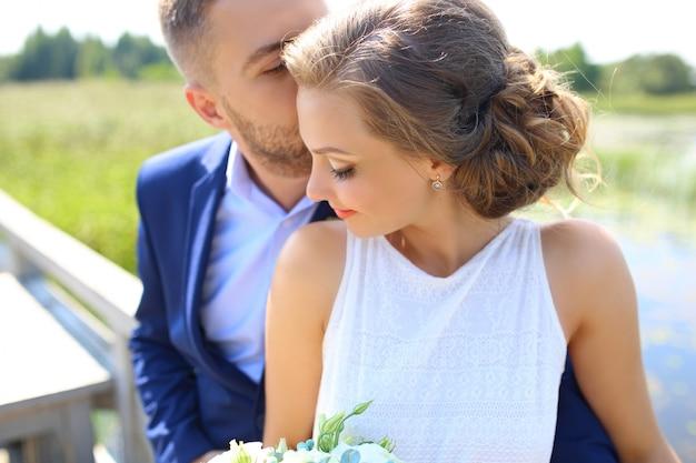 幸せなハンサムな新郎と日没のクローズアップでバルコニーにぴったりのbeautifyl花嫁