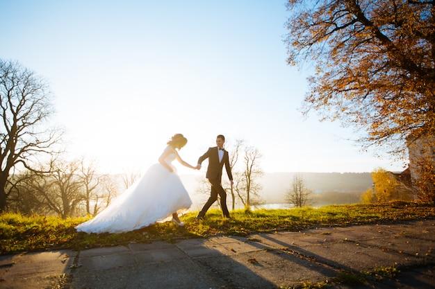 幸せなハンサムな新郎とbeautifyl花嫁の日没のクローズアップでバルコニーに抱いて