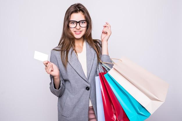 白い背景で隔離のクレジットカードで買い物袋を運ぶ美しい若い女性