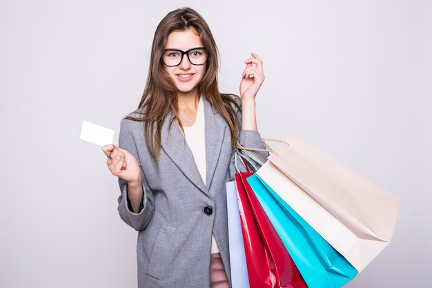 Beautilful young woman carrying shopping bags with credit card isolated on white background