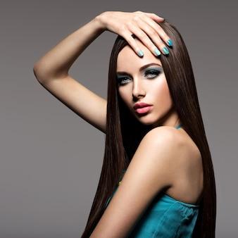 Beautiul donna elegante con trucco turchese e unghie - posa