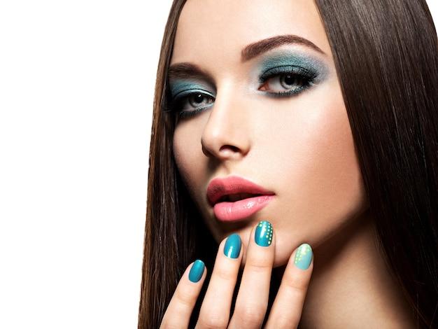 ターコイズブルーのメイクと爪を持つ美しいファッションの女性-白い壁に