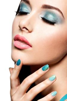 Красивая модная женщина с бирюзовым макияжем и ногтями - на белой стене