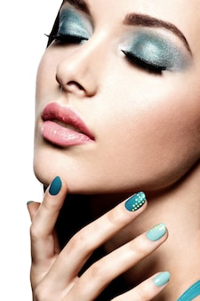 Beautiul fashion woman with turquoise make-up and nails  - on white wall