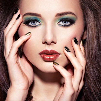 Beautiul woman with green make-up and creative color of nails