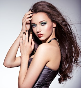 Beautiul donna con lunghi capelli castani e trucco verde e unghie