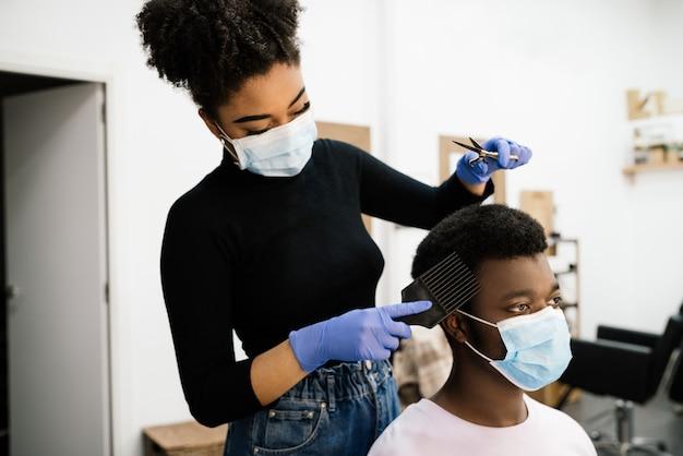 미용 아프리카 계 미국인 미용사는 코로나 바이러스 전염병으로부터 자신을 보호하기 위해 얼굴 마스크와 장갑을 착용 한 아프리카 계 미국인 남성 고객을 껍질을 벗기고 빗질합니다.