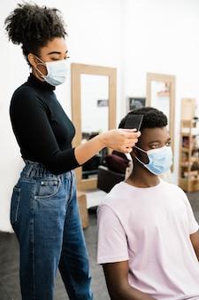 미용 아프리카 계 미국인 미용사는 코로나 바이러스 전염병으로부터 자신을 보호하기 위해 마스크와 장갑을 모두 착용 한 아프리카 계 미국인 남성 고객을 벗겨서 빗질합니다.