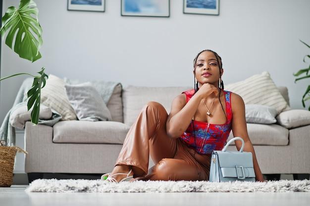 美しさアフロアメリカンモデルファッションブラジルの女性がハンドバッグで屋内でポーズします。