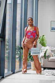 美しさアフロアメリカンモデルファッションブラジルの女性がハンドバッグで屋内でポーズします。 Premium写真