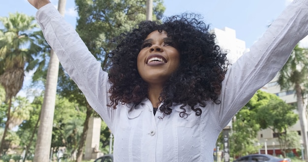 Beauty afro american woman looking at the horizon. pretty woman with curly hair feeling peaceful. cute black female enjoying fresh air thinking about life, optimistic.
