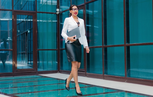 Beauty afro business woman in white jacket keep folder and walking on business building outdoors