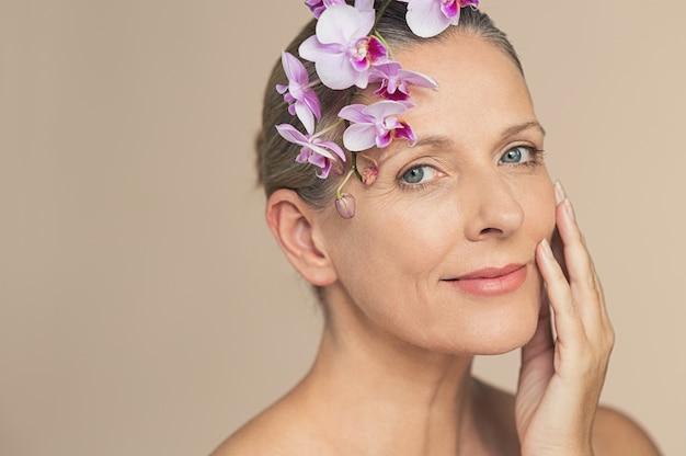 Красота возрасте женщина с розовыми орхидеями Premium Фотографии