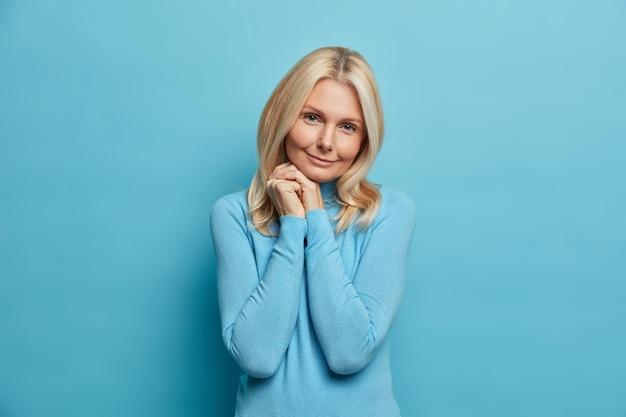 Concetto di bellezza e invecchiamento. affascinante donna adulta rugosa europea seria tiene le mani vicino al viso sorride teneramente