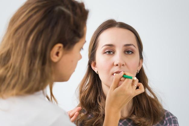 美容と化粧品のコンセプト-若い女性のプロのメイクアップを行うメイクアップアーティスト。