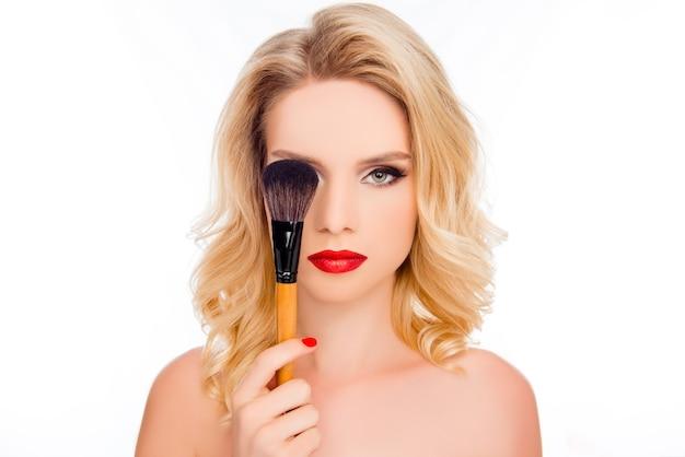 美容と美容のコンセプト。白いスペースに分離されたメイクブラシの後ろに目を隠す明るいメイクできれいな金髪の肖像画をクローズアップ