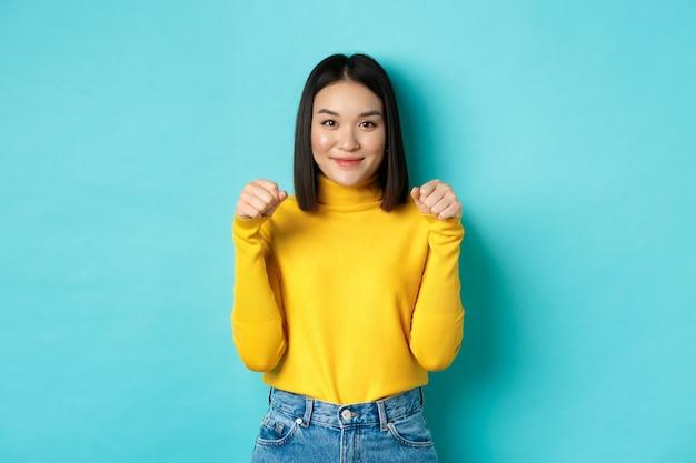 美容とファッションのコンセプト。黄色のプルオーバーで美しくスタイリッシュなアジアの女性、バナーやロゴを持っているかのように胸の近くで手を上げて、青い背景の上に立っています。