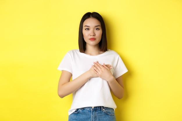 美容とファッションのコンセプト。心に手をつないで、カメラを思慮深く見て、魂の記憶を保ち、黄色の背景の上に立っている美しいアジアの女性。